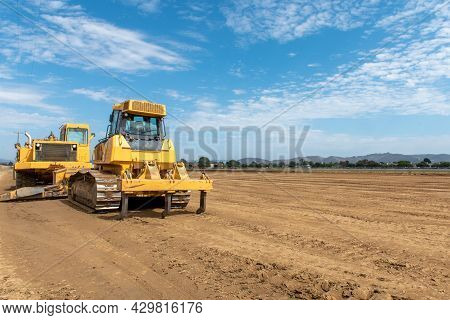 Heavy Grading Equipment Vehicles Resting After A Hard Days Work Grading The Farmland Field Down To C
