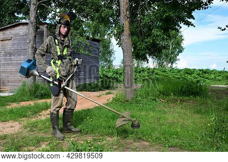 Worker In Special Protective Clothing With Lawn Mower In His Hands Mows Grass. Gardener Cuts Grass W