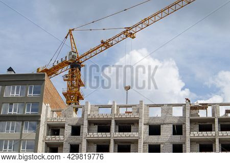 Construction Crane On An Unfinished Residential Building Against The Sun And Blue Sky. Housing Const