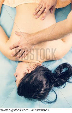 Masseur Doing Massage On Woman Back On A Blue Background In The Spa Salon. Top View. A Young Beautif