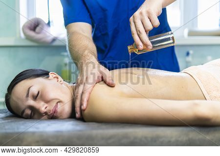 Masseur Preparing For Doing Aromatherapy Oil Massage In Spa Salon. Massage Therapist Pours Oil On Th