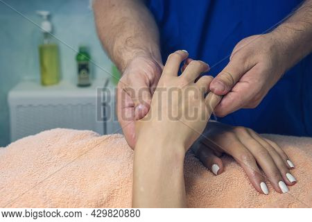 Detail Take Of A Massage Session On A Hand. A Professional Male Masseur Kneads The Hand Of A Young W