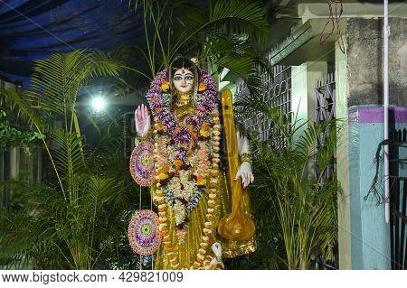 Idol Of Goddess Saraswati Being Worshipped Inside Pandal , A Temporary Temple, At Night. Colorful Li