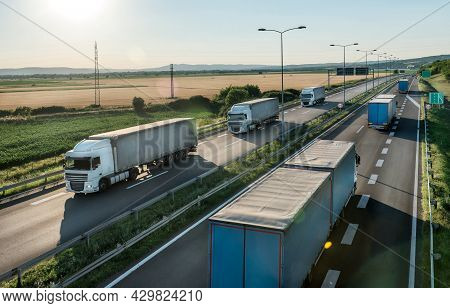 Transportation Trucks In Line Passing On A Highway On A Bright Blue Day. Highway Transit Transportat