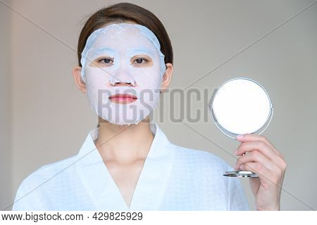 Portrait Of Young Woman Holding A Mirror While Applying Facial Mask For Enhance Her Skin. Facial Mas