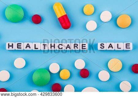 Medical Drugs And Pills On A Blue Background With The Inscription Healthcare. Marketable Healthcare