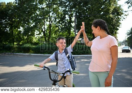 Smiling School Boy On Bicycle Giving High Five To His African American Mother. Child Coming Back To