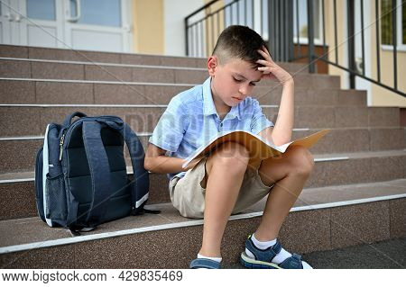 Puzzled Elementary School Student, Pupil, School Boy, Doing His Homework On A Notebook While Sitting
