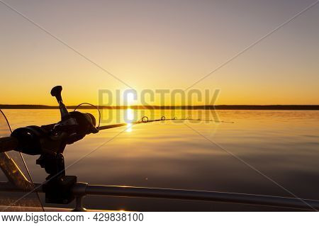 Fishing Rod Spinning With The Line Close-up. Fishing Rod In Rod Holder In Fishing Boat Due The Fishe
