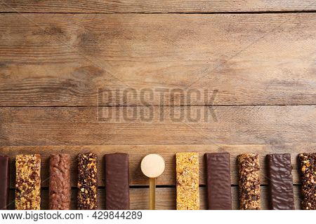 Different Tasty Bars And Scoop Of Protein Powder On Wooden Table, Flat Lay. Space For Text