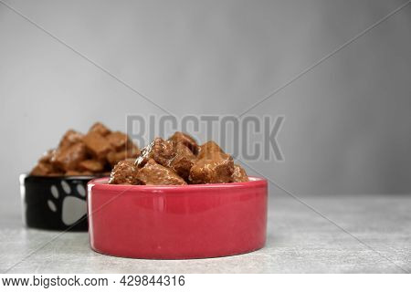 Wet Pet Food In Feeding Bowls On Light Grey Table, Space For Text