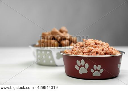 Wet Pet Food In Feeding Bowl On White Table, Space For Text