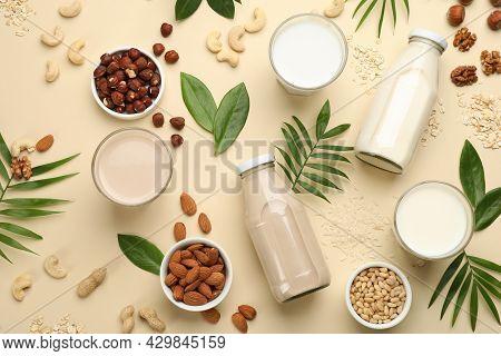 Different Vegan Milks And Ingredients On Beige Background, Flat Lay
