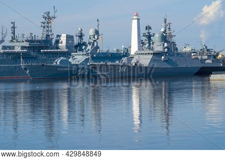Kronstadt, Russia - August 11, 2021: Ancient Lighthouse Among The Warships Of The Baltic Fleet On A
