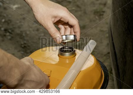 A Man Holds An Orange Gasoline Canister In His Hand Next To The Car Unscrews The Cork From The Fille