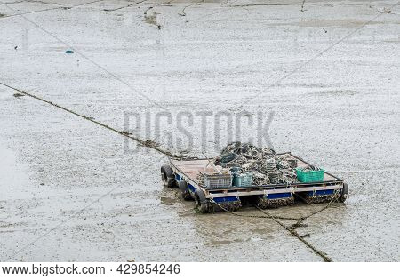 Small Flat Barge Loaded With Fishing Supplies Sitting In Mud At Low Tide.