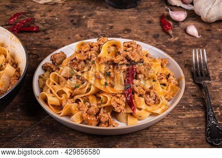 Traditional Rustic Italian-american Pasta With Sausage Stew, Served On A Plate On A Rustic Table.