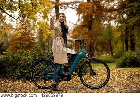 Young Woman With Electric Bicycle In Te Autumn Park