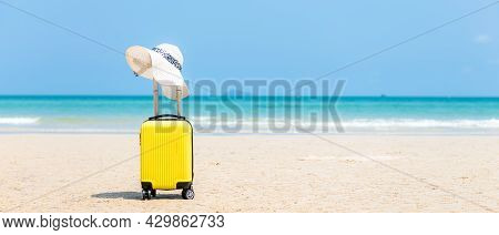 Summer Traveling And Tourism Planning With Yellow Suitcase Luggage With Big Hat Fashion In The Sand