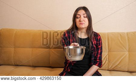 Sad Long Haired Woman In Checkered Shirt Collects Water Flowing From Ceiling Into Saucepot Sitting O