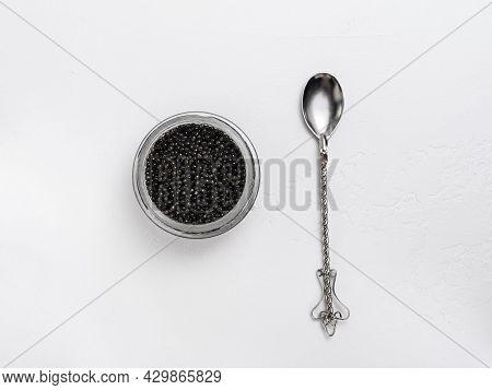 Glass Jar With Black Sturgeon Caviar And Vintage Spoon On White Background - Flatlay