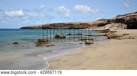 Beautiful Wild Beach Of Sand, Scattered Rocks And Calm Sea, Jandia, Fuerteventura Island, Spain