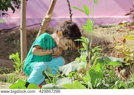 Close Up Photo Of A Small Indian Child Sitting In The Garden Pretending To Eat Raw Vegetables Or Fru