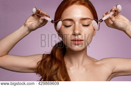 Sensual Young Woman With Red Hair And Freckles, Tenderly Massaging Her Facial Skin With Jade Rollers