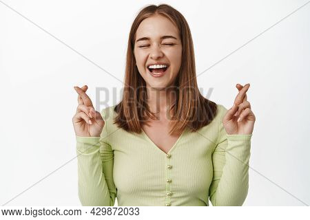 Cheerful Blond Girl Laughs And Makes Wish, Cross Fingers Optimistic, Praying For Good Luck, Wishing