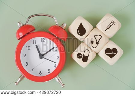 Red Analog Alarm Clock And Wood Cube With Medical Symbol On Green Background  For Health And Medical