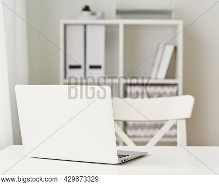 Contemporary Minimalist Interior. Mockup Of Office At Home. White Laptop, Chair And Bookshelf. Freel