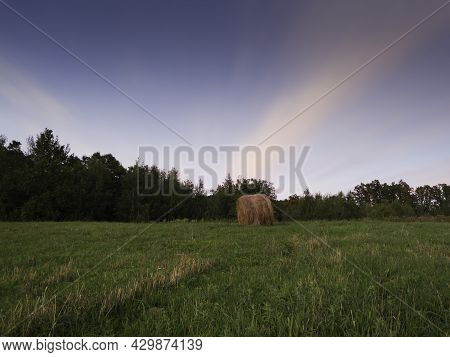 Long Exposure Shot Of Single Round Haystack In The Meadow During Summer Blue Hour At Evening, Cattle