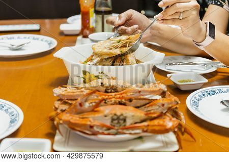 Asian Woman Hand Holding Shrimp With Spoon And Fork At Dinner Table