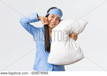 Pleased Beautiful Asian Girl In Blue Pyjamas And Sleeping Mask, Lying In Bed And Hugging Pillow, Smi