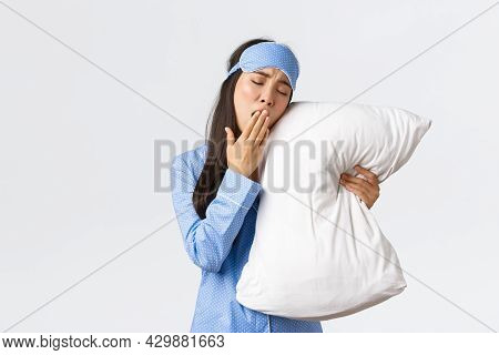 Tired Silly Asian Girl In Blue Pyjama And Sleeping Mask, Lying In Bed And Hugging Pillow, Yawning Ex