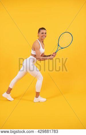 Happy Young Girl In Sportswear Running With Racket. Sportswoman. Energetic Woman