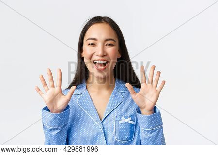 Close-up Shot Of Happy Attractive Asian Woman In Blue Pyjama Showing Ten Fingers And Smiling White T