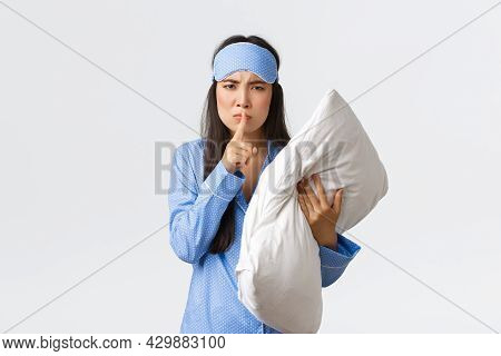 Angry Displeased Asian Girl In Sleeping Mask And Pyjamas, Holding Pillow And Frownign Disturbed, Shu