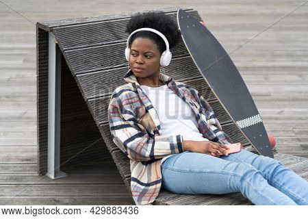 African Female Listen To Music Outdoors Dressed In Trendy Casual Clothes With Skateboard Sitting On