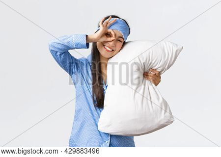 Joyful Enthusiastic Beautiful Asian Girl In Blue Pyjama And Sleeping Mask, Hugging Pillow And Smilin