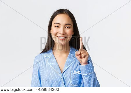 Close-up Shot Of Happy Attractive Asian Woman In Blue Pyjama Showing Number One, One Finger And Smil