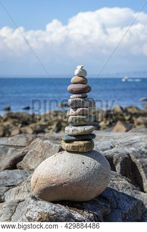 Stack Of Stones Near The Sea With Blue Sky Background.