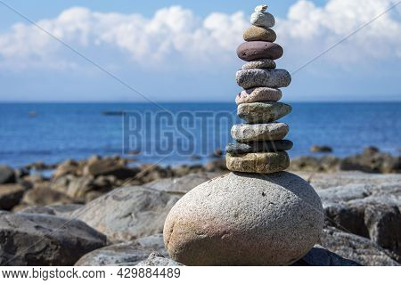 Stack Of Stones With Blue Sea And White Cloud Background.