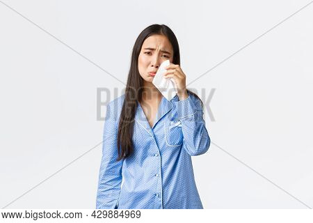 Distressed Silly Asian Girl In Blue Pajamas Feeling Heartbroken, Staying In Bed In Bad Mood, Wipe Te