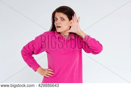 I Cant Hear You. Beautiful Young Woman Listening Gossips And Holding Her Hand Near The Ear While Iso