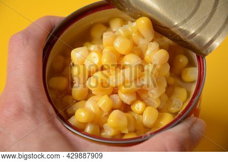 Open Tin Can In Hand With Corn Kernels On Yellow Background