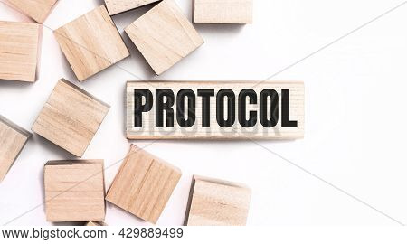 On A Light Background, Wooden Cubes And A Wooden Block With The Text Protocol. View From Above