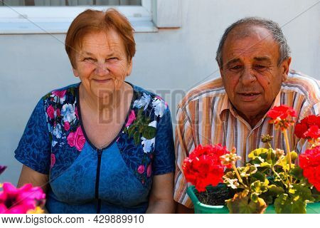 Elderly Couple Smiling In Summer Day. Happy Elderly Pair Of Husband And Wife Seating On Flowers Gard