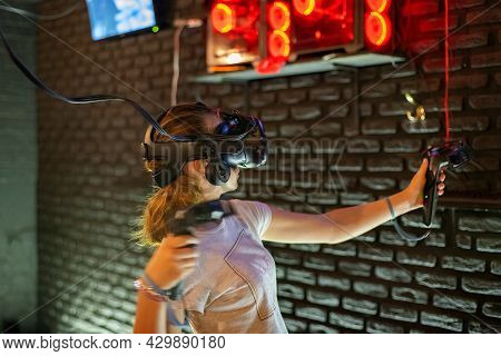A Girl Plays In A Virtual Reality Helmet And Holds Joysticks In Her Hands While Playing Games In A C