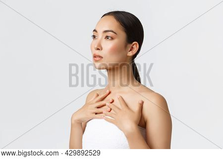 Profile Of Feminine Sensual Young Asian Woman In White Towel Looking Upper Left Corner And Touching